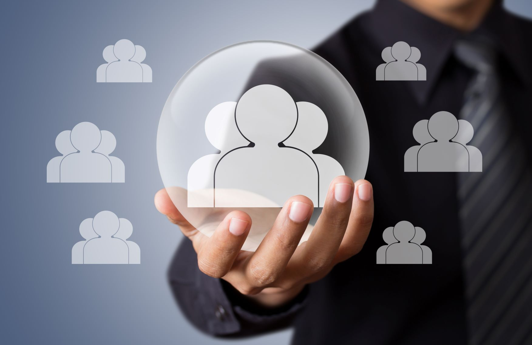 man in a dark business suit holding icons of a group of people in a protective bubble