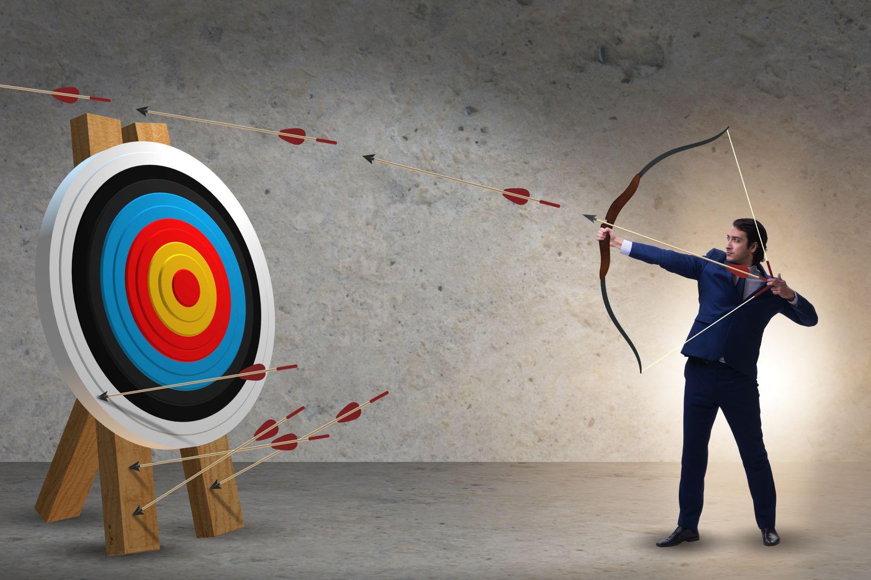 businessman shooting an arrow at a large target